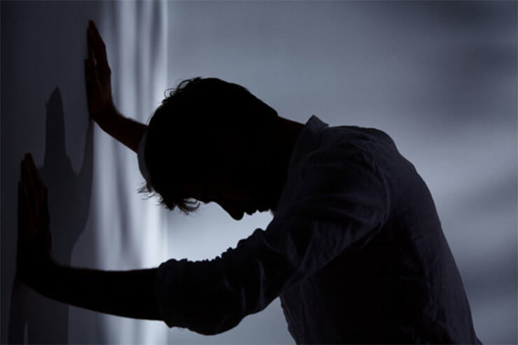 Man leaning against a wall. The outward signs of a mental illness are often behavioural