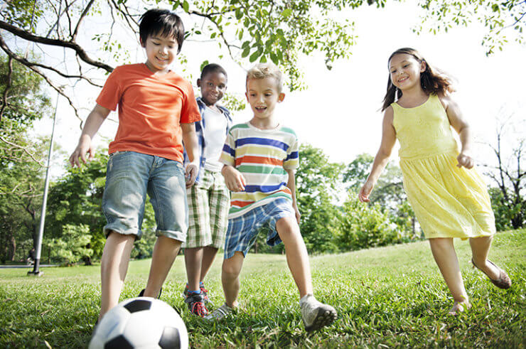 happy children playing football outside 770px